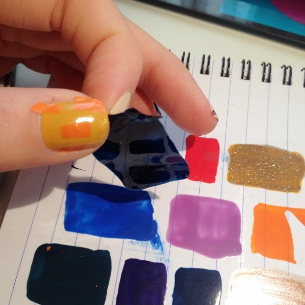 Carefully peeling nail polish swatches from sellotape on paper