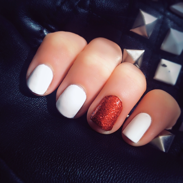 Matte white and red glitter nails on a black leather jacket background