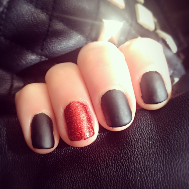 Matte Black and red glitter nails on a black leather jacket background